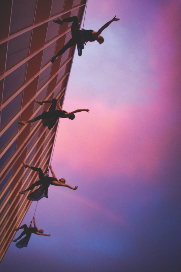 Aerial dancers on the side of a building