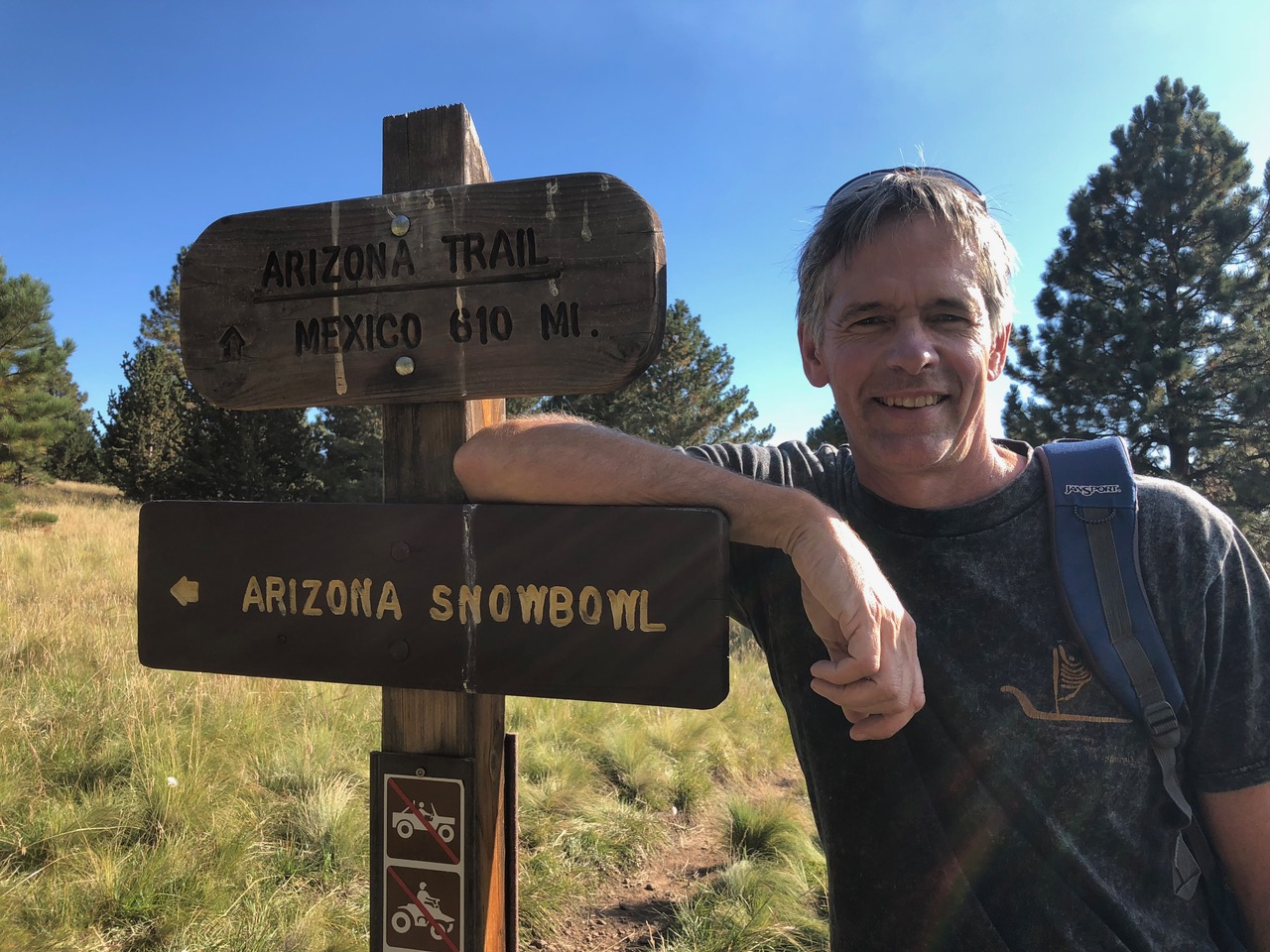Scientist next to hiking trail sign