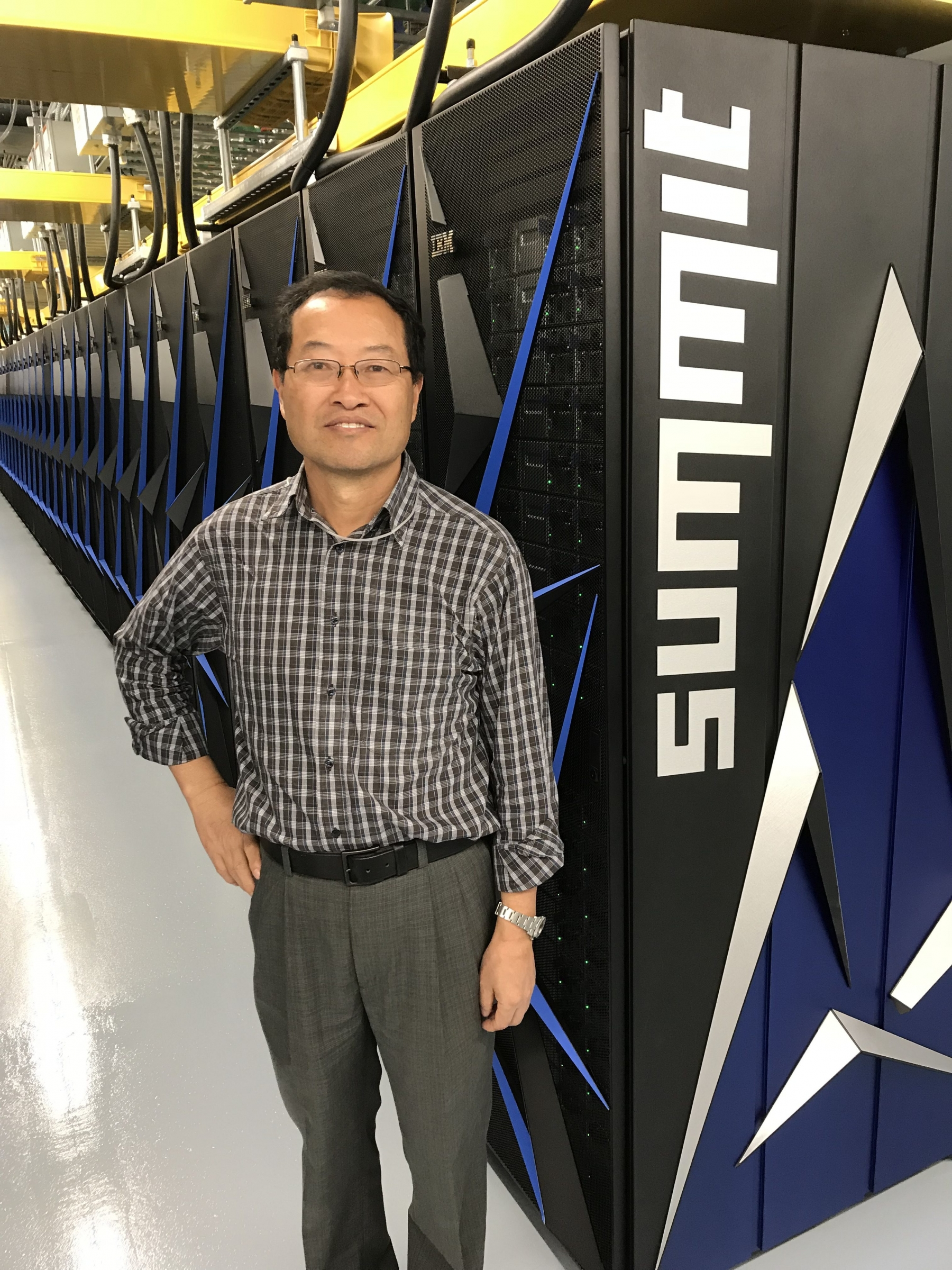 Picture of Yiqi Luo with supercomputer