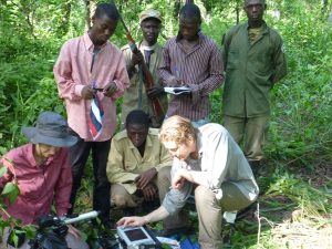 Picture of scientists gathering data in a rain forest. Armed guards in the background
