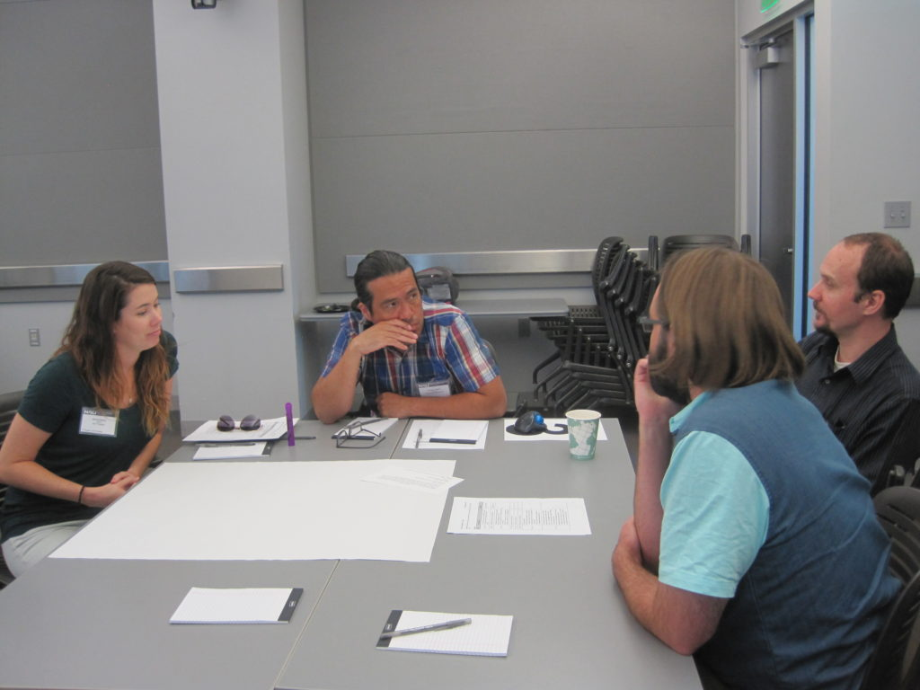 Students, postdocs, and professors having a discussion around a table