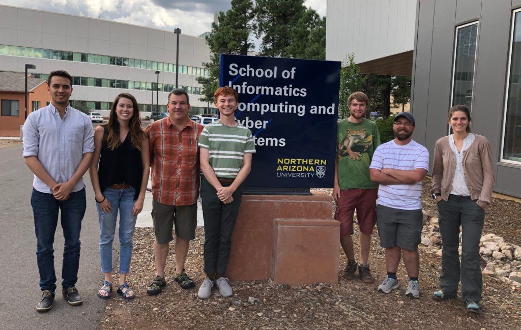 This is a picture of the 7 students in the first cohort of PhD students in the T3 option in Ecological and Environmental Informatics. The students are standing around the School of Informatics, Computing, and Cyber Systems sign.
