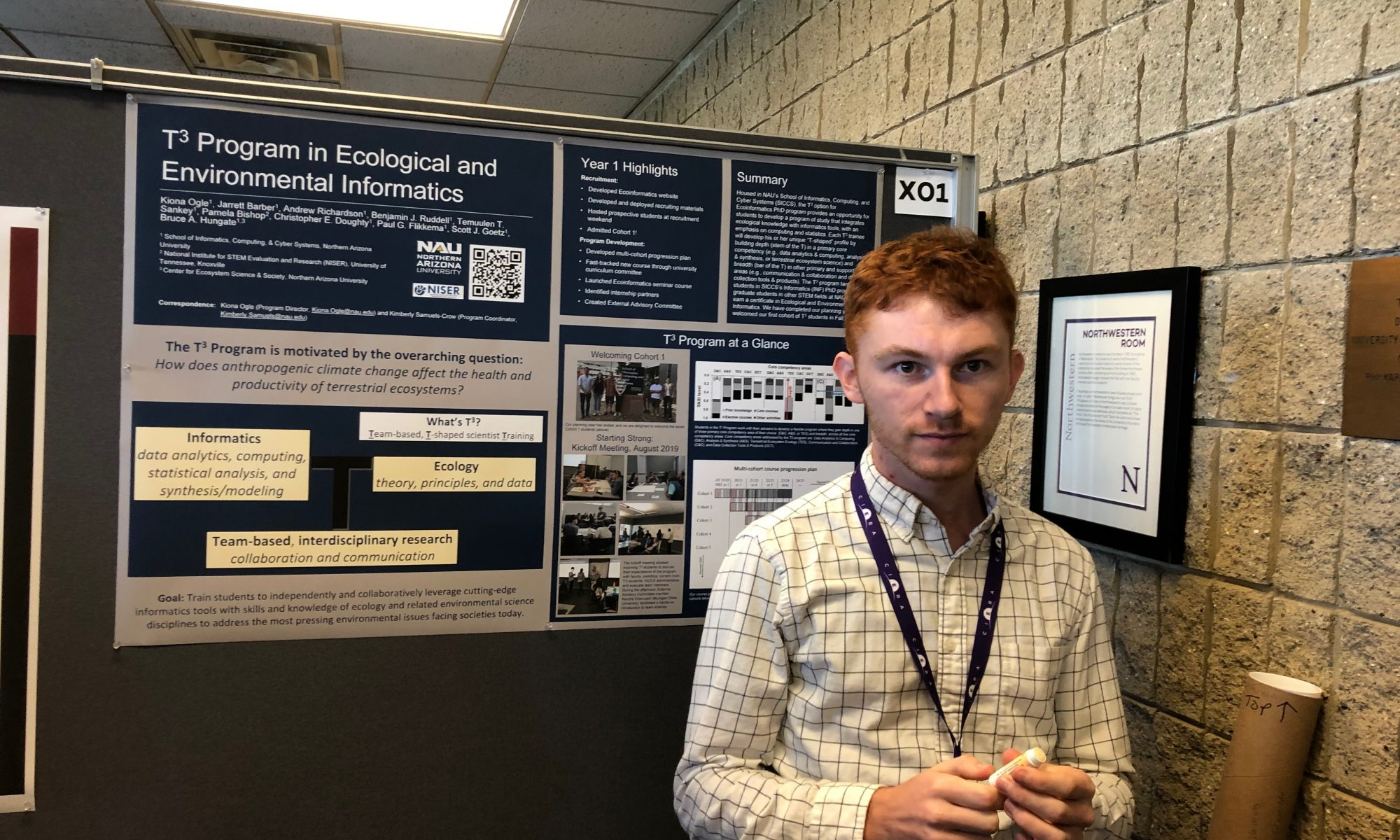 Male grad student in front of poster