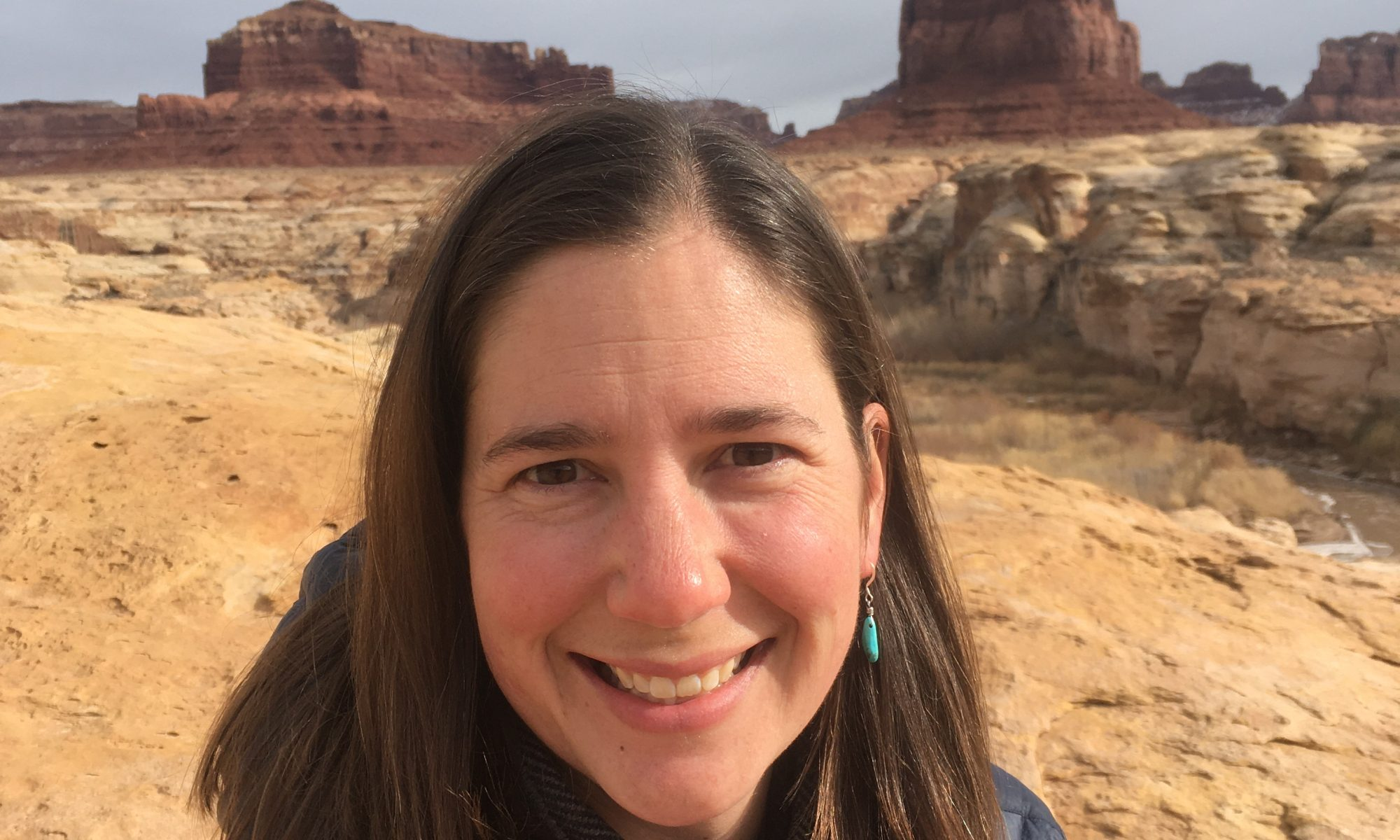 Female graduate student in front of monuments in Monument Valley