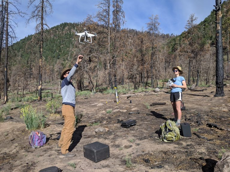 Two scientists test a drone in the field