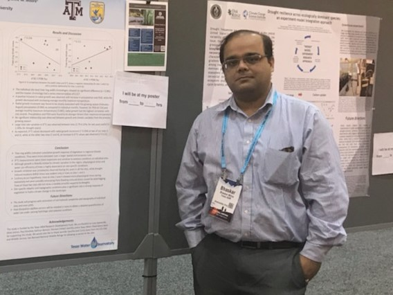 Postdoc standing by poster